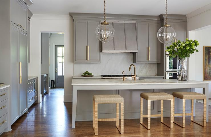 gray-shaker-kitchen-cabinets-long-brass-cabinet-pulls-gold-counter-stools